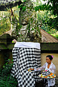 Mature woman with oblation in front of a stone figure, Amandari Hotel, Yeh Agung, Bali, Indonesia, Asia