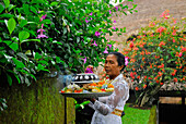 Mature woman with oblation in the garden of the Amandari Hotel, Yeh Agung, Bali, Indonesia, Asia