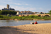 Young couple sitting along the banks of the river Loire, Saint Cyr et Sainte Julitte Cathedral in the background, Bridge over the river Loire, The Way of St. James, Chemins de Saint Jacques, Via Lemovicensis Nevers, Dept. Nièvre, Burgundy, France, Europe