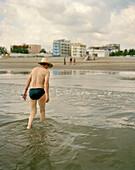 A man wearing a hat coming out of the water, Playa Boca del Rio, Veracruz, Veracruz province, Mexico, America
