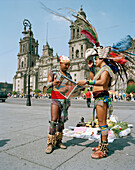Men wearing aztec costumes reading a newspaper at the Zocalo in front of the cathedral, Mexico City, Mexico, America