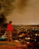A man looking from Barrio Xochimilco at the lights of Mexico City, Mexico, America