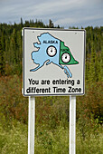 Time zone change sign marker at border of Yukon Territory Canada and Alaska AK U S United States Alaska Highway ALCAN Al-Can
