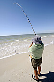 Senior man fishing for recreation in the Gulf of Mexico at Naples Florida