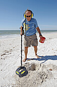 Senior male uses metal detector to find objects on a beach at Naples Florida