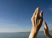 Adult, Adults, Aged, Arms raised, Blue, Blue sky, Color, Colour, Contemporary, Daytime, Detail, Details, Elder, Elderly, Exterior, Female, Free, Freedom, Gesture, Gestures, Gesturing, Hand, Hands, Horizon, Horizons, Human, Mature adult, Mature adults, Mat