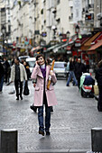 A young woman holding a baguette and talking on her cell phone on the street of Paris. Paris. France