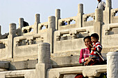 A mother and her child in behind stone carved railings of Round Altar in Temple of Haven. Beijing. China