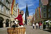 Cyclist with dog, Prinzipal market, Muenster, Muensterland, North Rhine-Westphalia, Germany