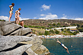 Young people jumping off the cliffs at the beach of Cavoli, Elba, Italy