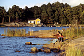 A man and a child sitting at the shore of a skerry in the light of the evening sun, South Finland, Europe