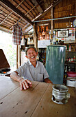 Laughing man sitting at a table, Ko Pha Ngan, Thailand