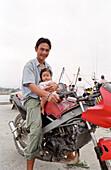 Father and child on a motorbike, Thong Sala, Ko Pha Ngan, Thailand