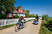 Cyclists passing thatched house, Steenodde, Amrum island, North Frisian Islands, Schleswig-Holstein, Germany