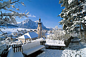 Snow covered houses and church under blue sky, Kastelruth, South Tyrol, Italy, Europe