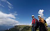 Zwei Männer mit Helm vor Bergen und blauem Himmel, Seiser Alm, Eisacktal, Südtirol, Italien, Europa