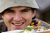 Laughing man and a plate with mushroom dish, Alpe di Siusi, South Tyrol, Italy, Europe