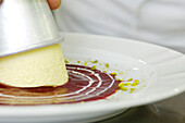 Cook preparing the dessert, Panna cotta with raspberry sauce, Gastronomy, South Tyrol, Italy