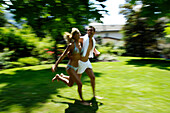 A young couple running accross the grass, Motion, Park, South Tyrol, Italy