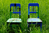 Two painted chairs in the middle of a meadow, Art at the Farm, Contemporary artist Berty Skuber, Prackfolerhof, Völs am Schlern, South Tyrol, Italy
