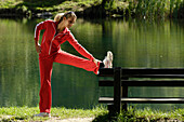 Young woman doing stretching exercises on a bench near a lake, Training, Jogging, Fitness, South Tyrol, Italy
