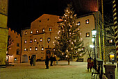 Kastelruth in Winter, village square piazza Kraus, Krausplatz with Christmas tree at night, Kastelruth, Castelrotto, South Tyrol, Italy