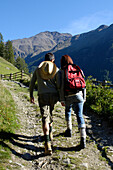 A man and a woman with backpack on a hiking trail in the mountains, Schnals valley, Val Venosta, South Tyrol, Italy, Europe