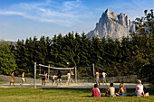 Teenagers playing volleyball in the sunlight, Kastelruth Seis, Telfen, South Tyrol, Italy, Europe