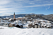 Snow covered houses and church of the village Kastelruth in the sunlight, South Tyrol, Italy, Europe