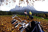 Man and woman with golf bag on golf court Kastelruth Alpe di Siusi in autumn, Sciliar, South Tyrol, Italy, Europe