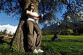 A woman with golf club and sunglasses leaning on a tree, golf court Kastelruth Alpe di Siusi, Sciliar, South Tyrol, Italy, Europe