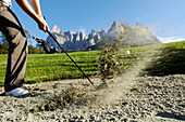 A woman hitting the golf ball out of the bunker, golf court Kastelruth Alpe di Siusi, Sciliar, South Tyrol, Italy, Europe