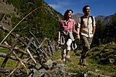 A mid adults couple hiking in the mountains in summer, Val Venosta, Vinschgau, South Tyrol, Italy, Europe