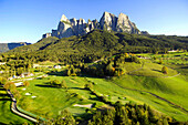 Golf court in the sunlight in front of mountains, Golf court Kastelruth Seiser Alm, Sciliar, South Tyrol, Italy, Europe