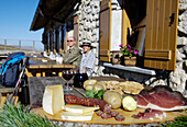 Snack in front of an alpine hut in the sunlight, Alpe di Siusi, Valle Isarco, South Tyrol, Italy, Europe