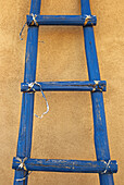 A blue ladder leans against an adobe wall at Ghost Farm, New Mexico. Ghost Farms was the home of American painter Georgia O'Keefe.