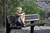 A caucasian boy, 5 to 10, seated on a bench looking unhappy