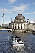 Museumsinsel, Mitte area, Berlin, Germany. View from Weidendammbrücke east to Bodemuseum, sightseeing ferry. Television tower in the background left.