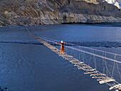 Trekker makes the scary crossing of the Hunza River in the Karakoram Mountains of Pakistan on rickety footbridge