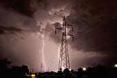 Lightning strikes during thunder storm over a power line