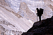 A trekker is looking down into a huge canyon formed buy the Zanskar river.In the winter time this Trek is called Chaddar by the locals.