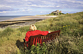 Bamburgh Beach and Castle, with woman wearing a red jacket seated in the foreground, Northumberland, England, UK