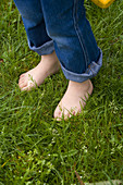 Anonymous, Barefeet, Barefoot, Blue jean, Blue jeans, Chill out, Chilling out, Close up, Close-up, Closeup, Color, Colour, Comfort, Comfortable, Contemporary, Country, Countryside, Daytime, Denim, Exterior, Feet, Field, Fields, Foot, Grass, Grasses, Grass