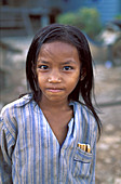 In order to support her family, this little girl sells cigarettes. Poverty is a problem in rural Cambodia.