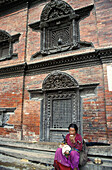 A local nepali woman rests in one of the old streets of Patan, Kathmandu valley, Nepal