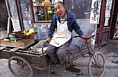 A man rests in a narrow street in the old city of Ping Yao. Shanxi, China