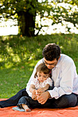 Father and daughter (2-3 years) sitting on grass, English Garden, Munich, Bavaria, Germany