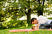 Father and daughter (2-3 years) playing on grass, English Garden, Munich, Bavaria, Germany