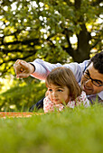 Father and daughter (2-3 years) lying on grass, English Garden, Munich, Bavaria, Germany
