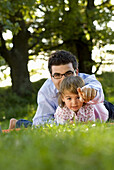 Father and daughter (2-3 years) lying in meadow, English Garden, Munich, Bavaria, Germany